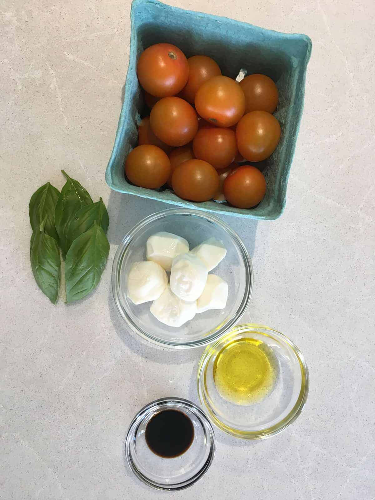 Orange cherry tomatoes, fresh basil leaves, baby mozzarella balls, olive oil and balsamic vinegar atop a light grey marble countertop