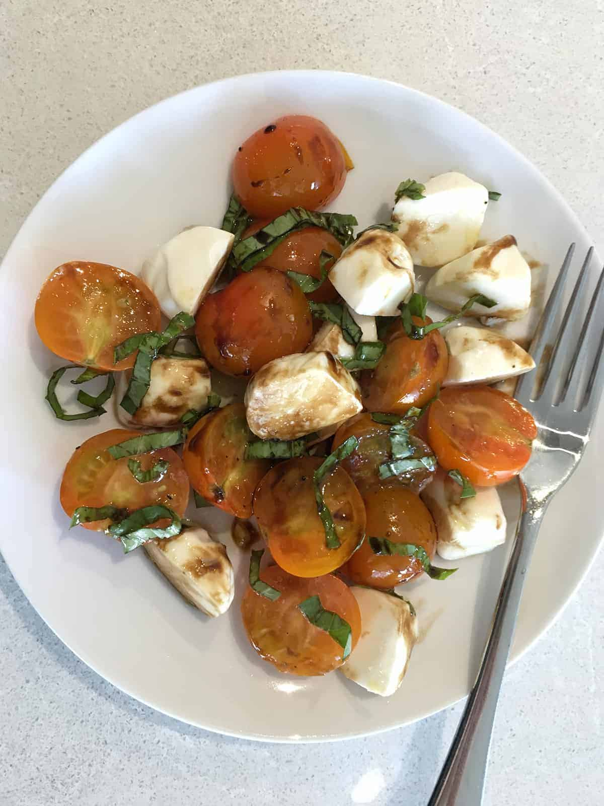 Cherry tomato Caprese salad on a white plate atop a marble countertop