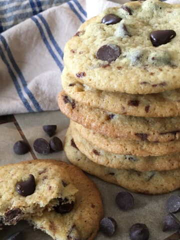 Chocolate chip cookies in a stack with a blue and tan plaid napkin