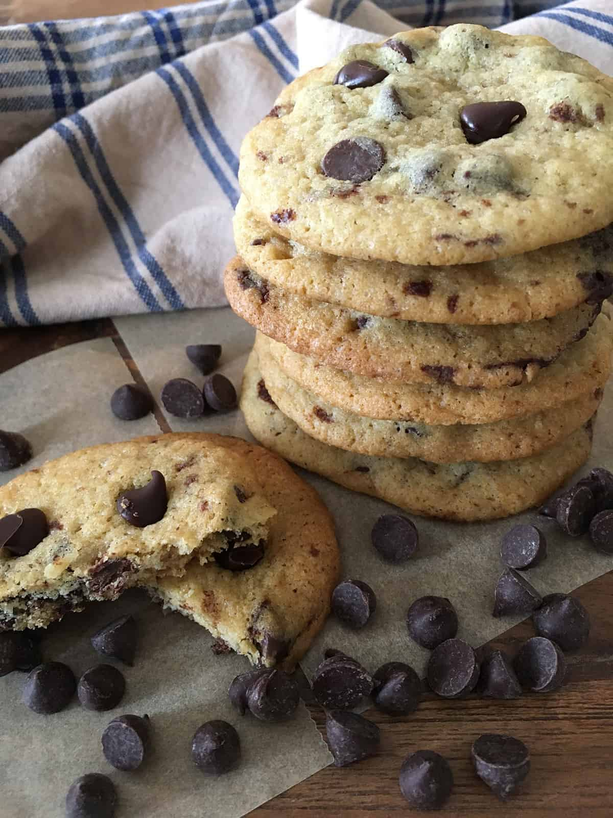 Chocolate chip cookies in a stack with a blue and tan plaid napkin on a dark brown table
