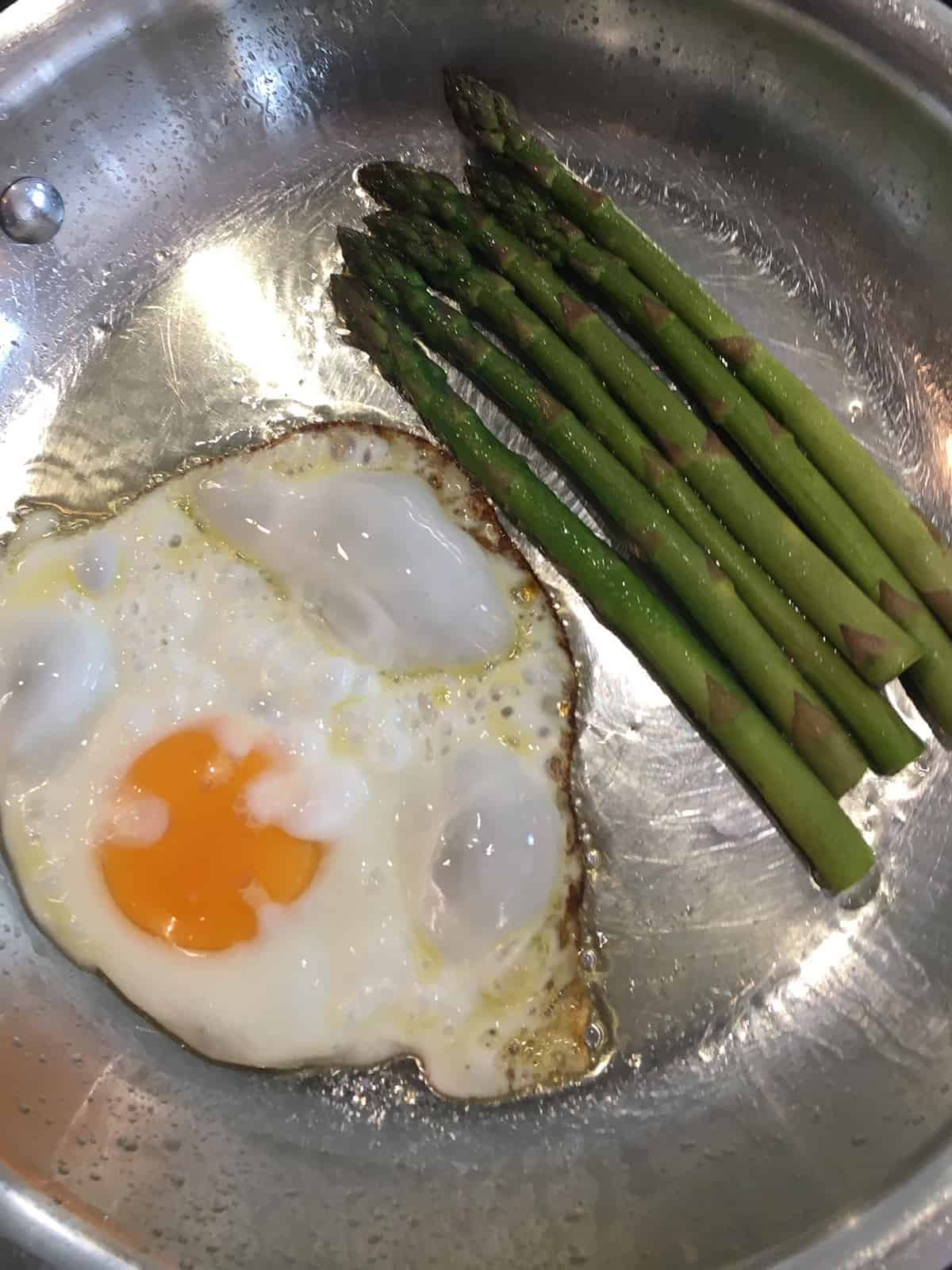 A sunny side up egg and six asparagus spears frying in ghee in a stainless steel skillet