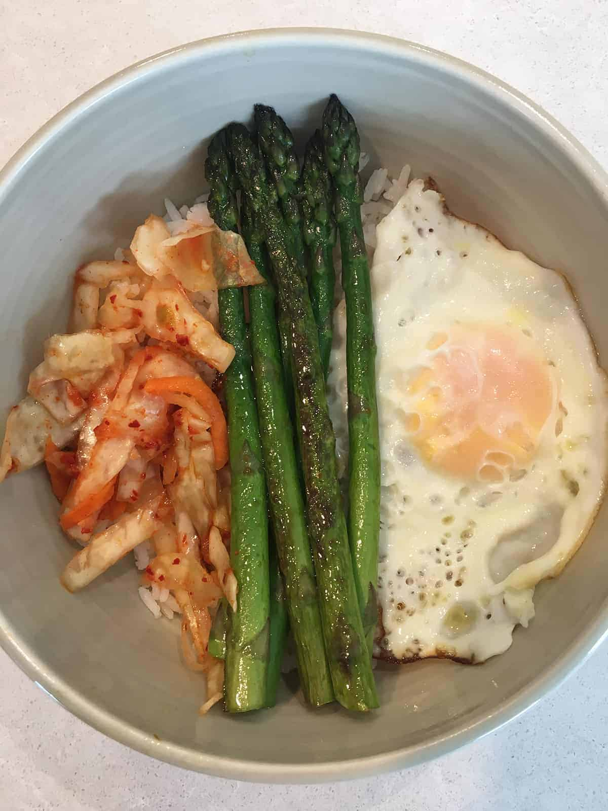 Kimchi, fried egg and asparagus spears over white rice in an off-white bowl atop a light grey marble countertop