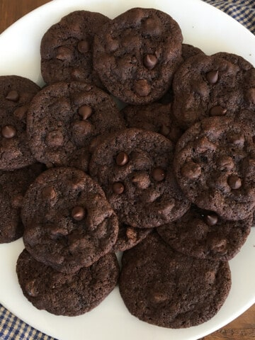 Freshly baked soft and chewy double chocolate chip cookies on a white serving plate
