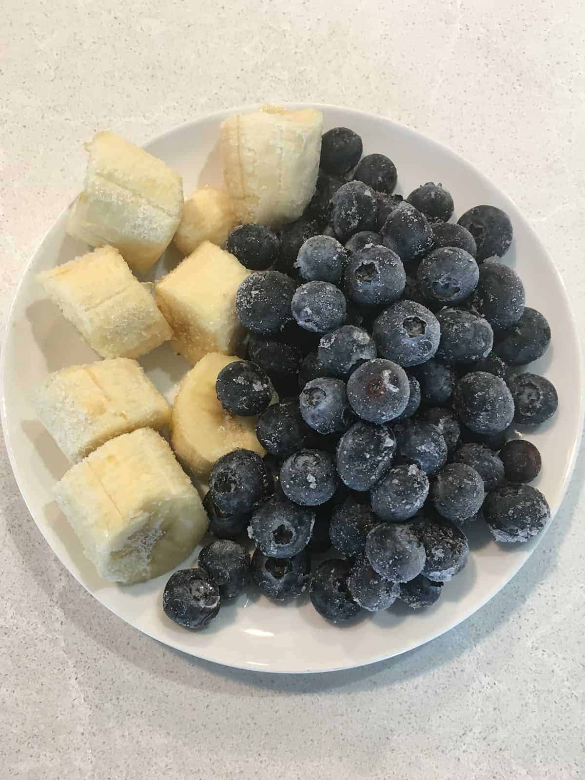 Chopped frozen banana chunks and frozen blueberries on a small white plate atop a light grey marble countertop