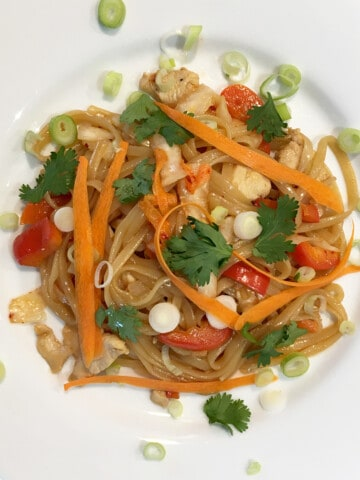 Quick kimchi noodles garnished with fresh cilantro and scallions on a white plate