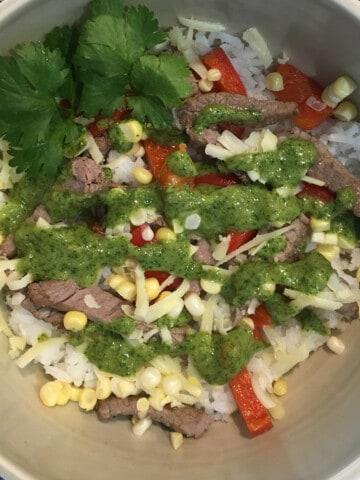 Veggie and rice steak bowl with cilantro lime pesto in a tan ceramic bowl