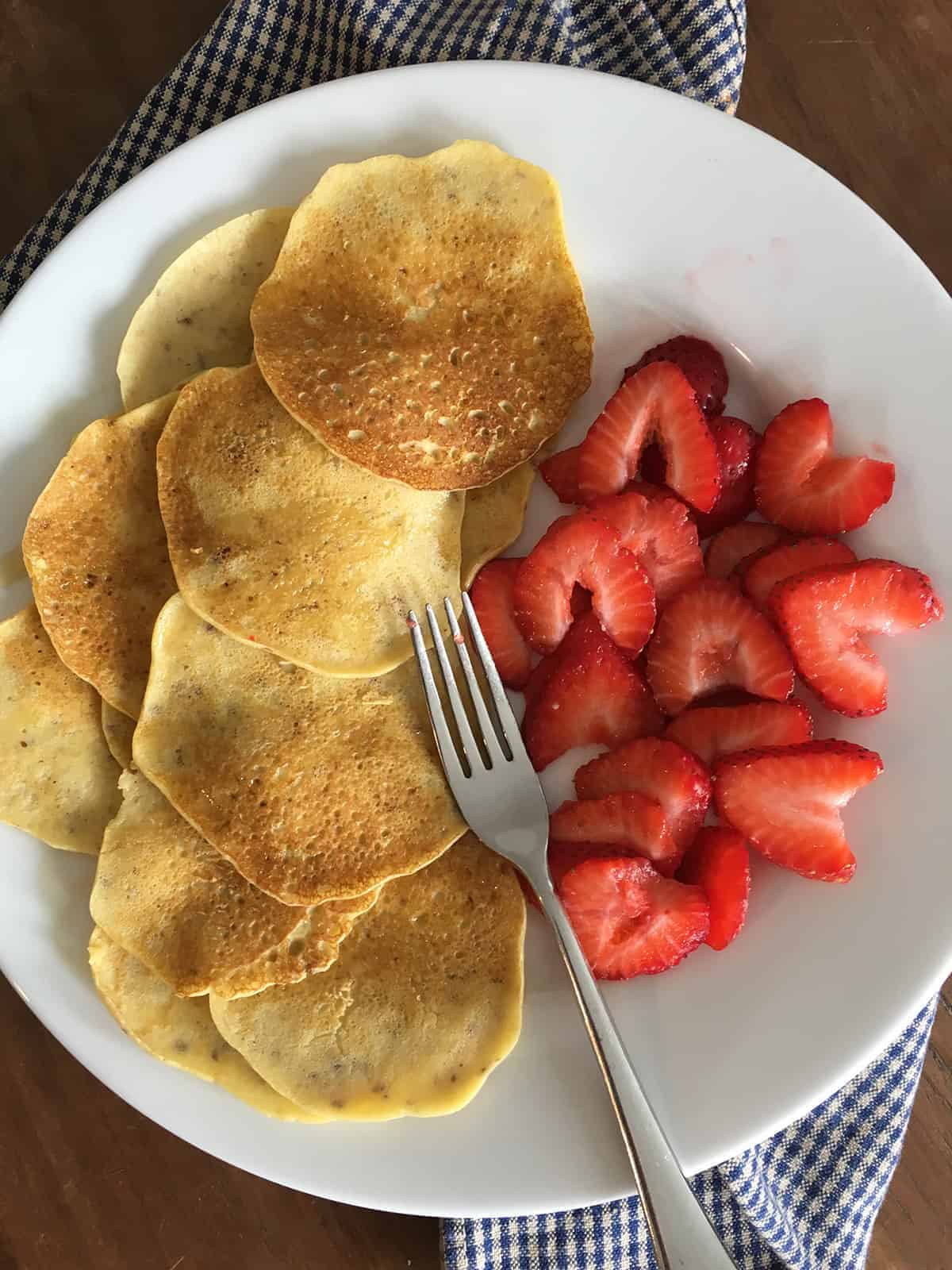 Mini almond flour crepes with fresh sliced strawberries and a fork on a white plate