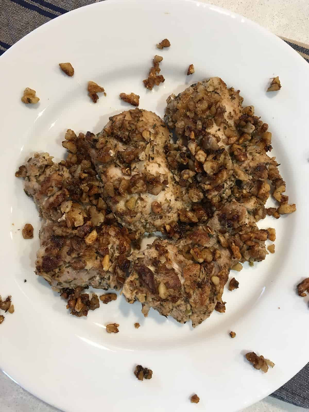 Walnut and herb crusted chicken thighs on a white serving platter