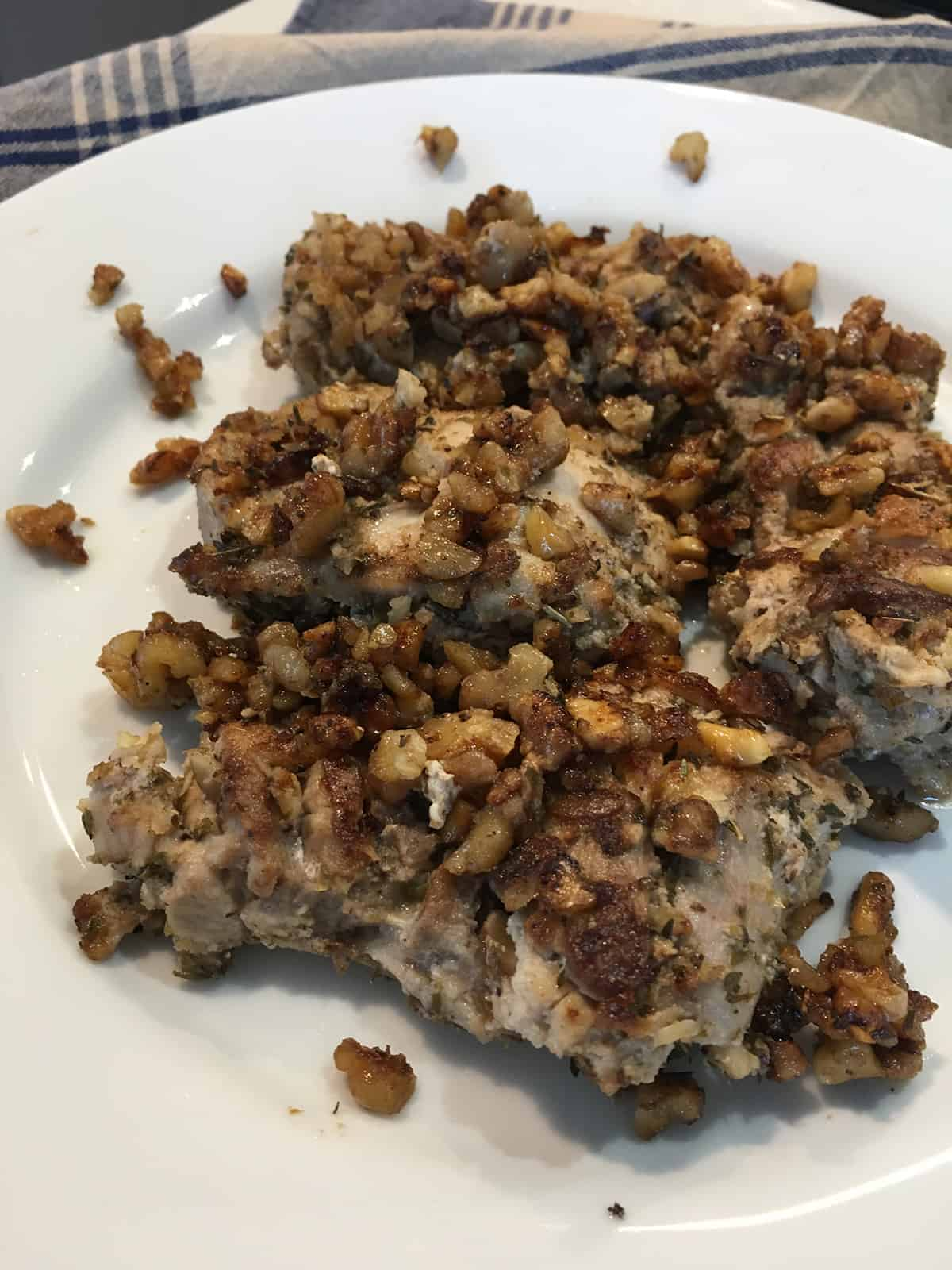 Close up of walnut and herb crusted chicken thighs on a white serving plate with  blue and tan plaid napkin