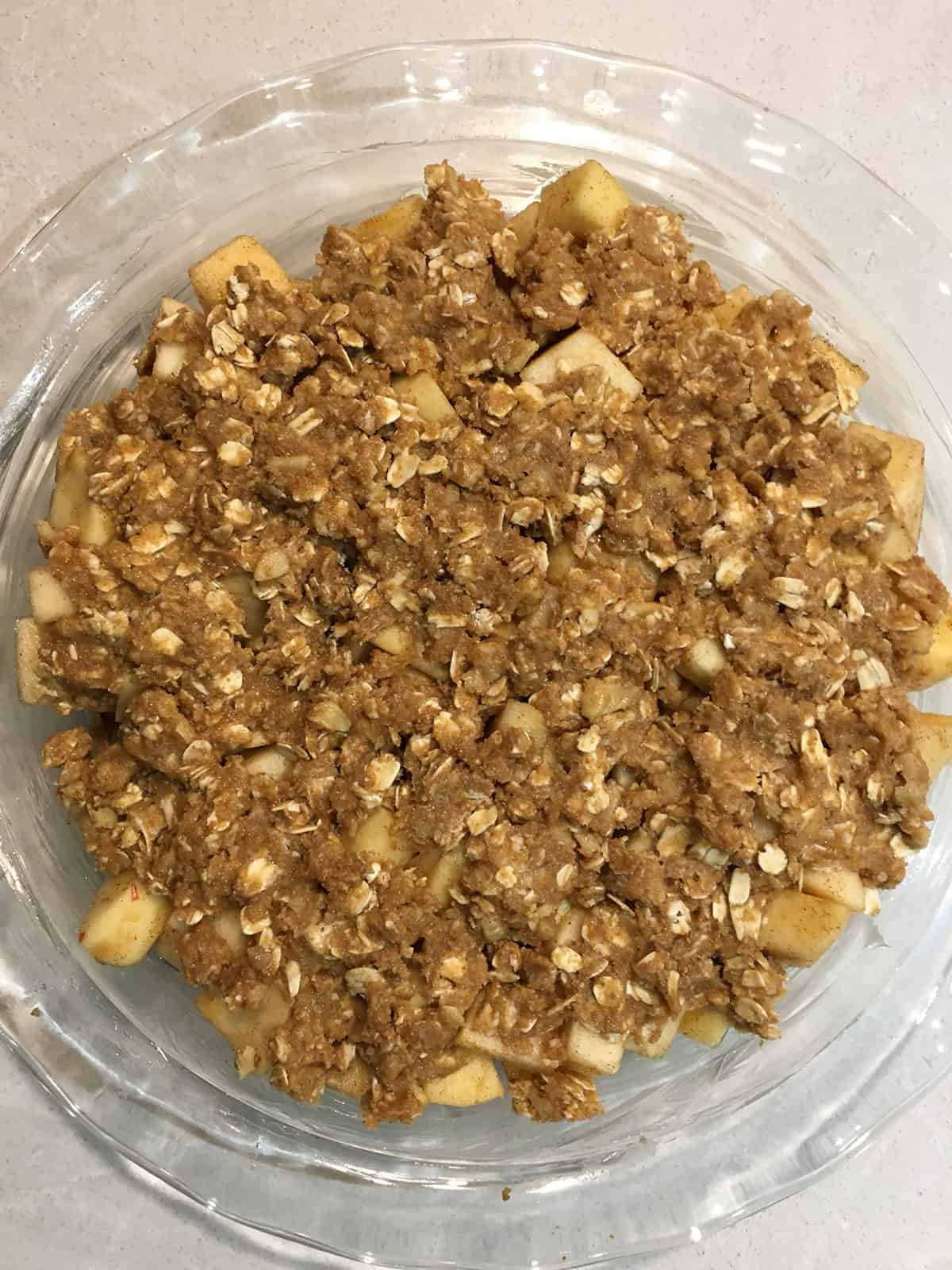 Apple crisp in a glass baking dish ready to go into the oven