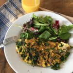 Dandelion greens omelette with mixed salad greens on a white plate with glass of orange juice