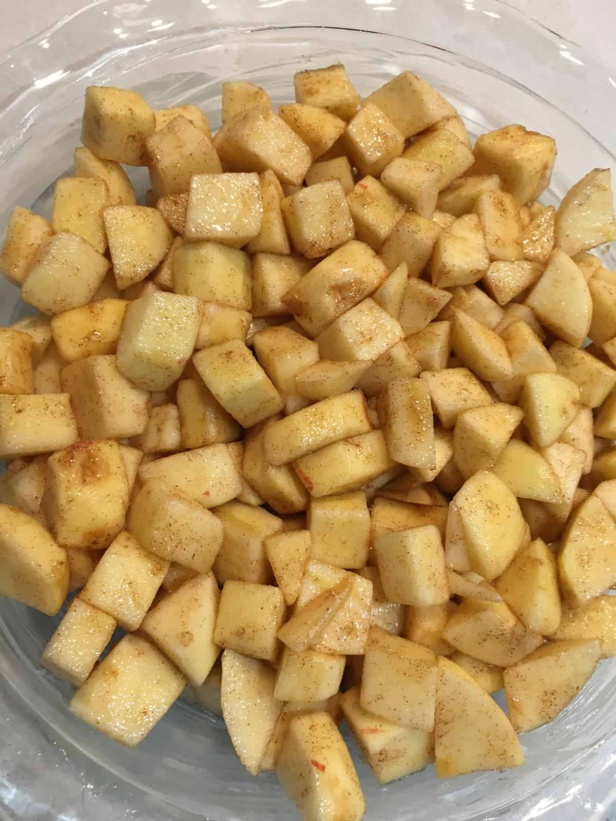 Chopped and prepared apples in a buttered glass baking dish