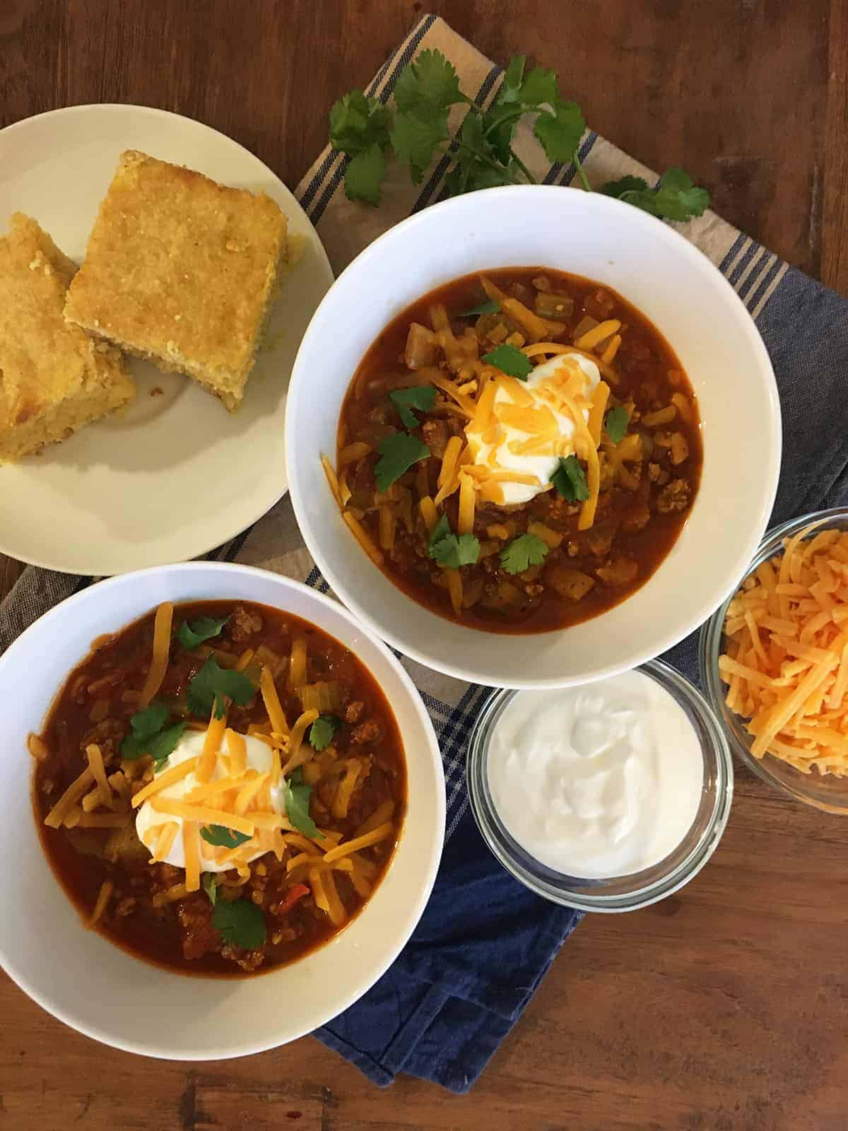 Quick and easy chili with a dollop of sour cream and shredded cheese in two white serving bowls