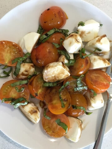 Cherry tomato Caprese salad on a white plate