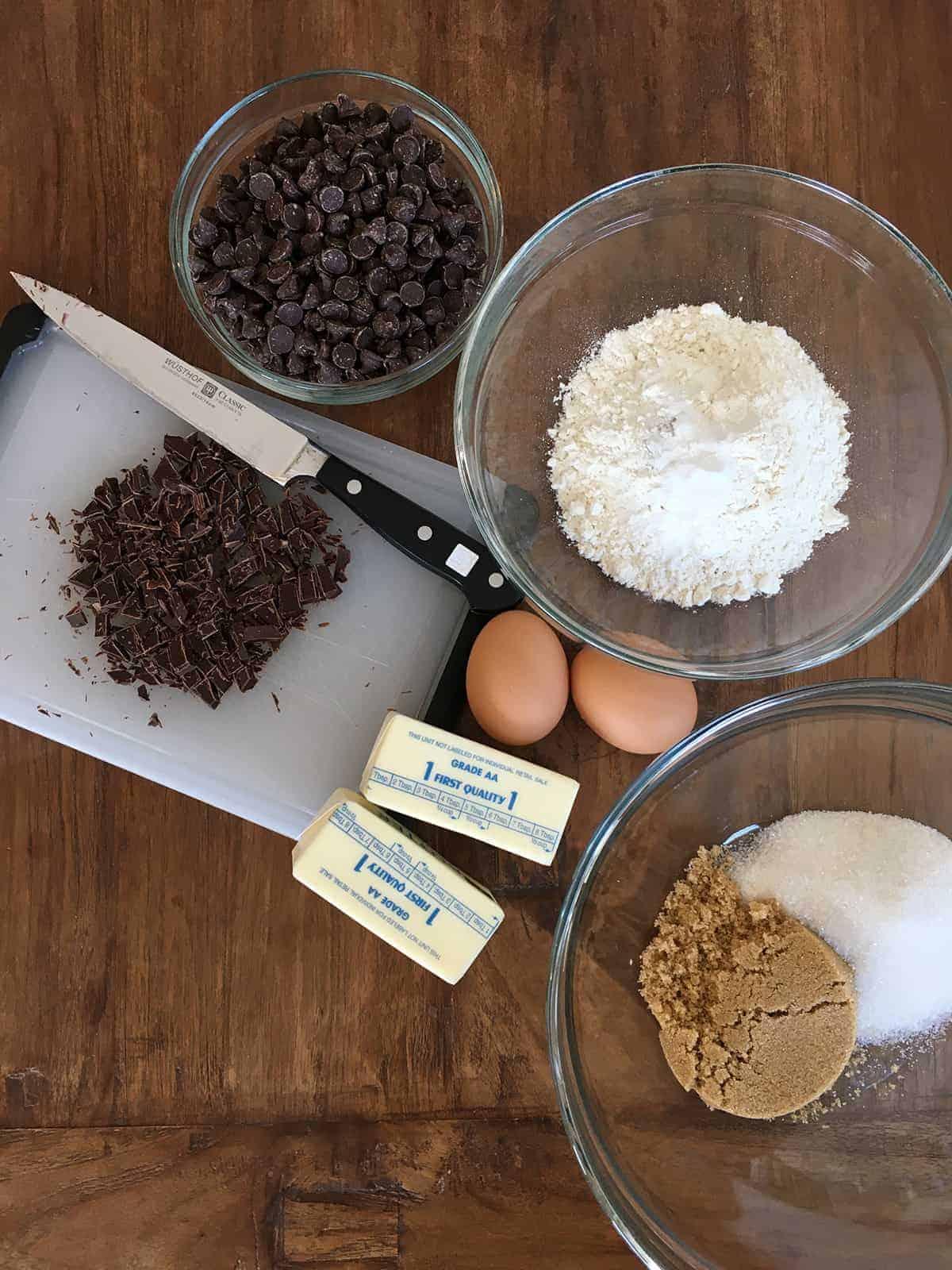 Chocolate chip cookie ingredients on a dark brown table