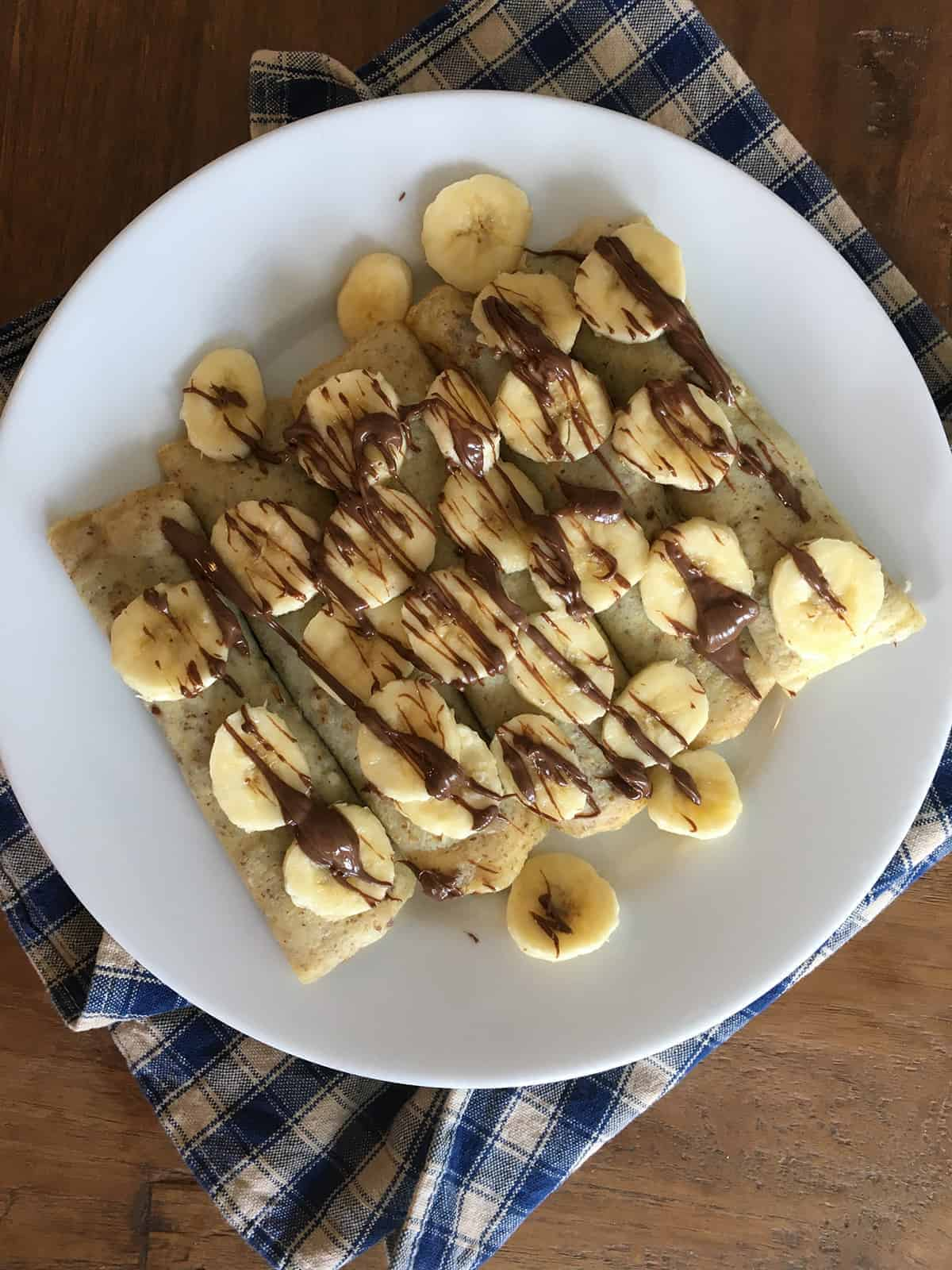 Banana Nutella Crepes on a white plate with a tan and blue plaid napkin