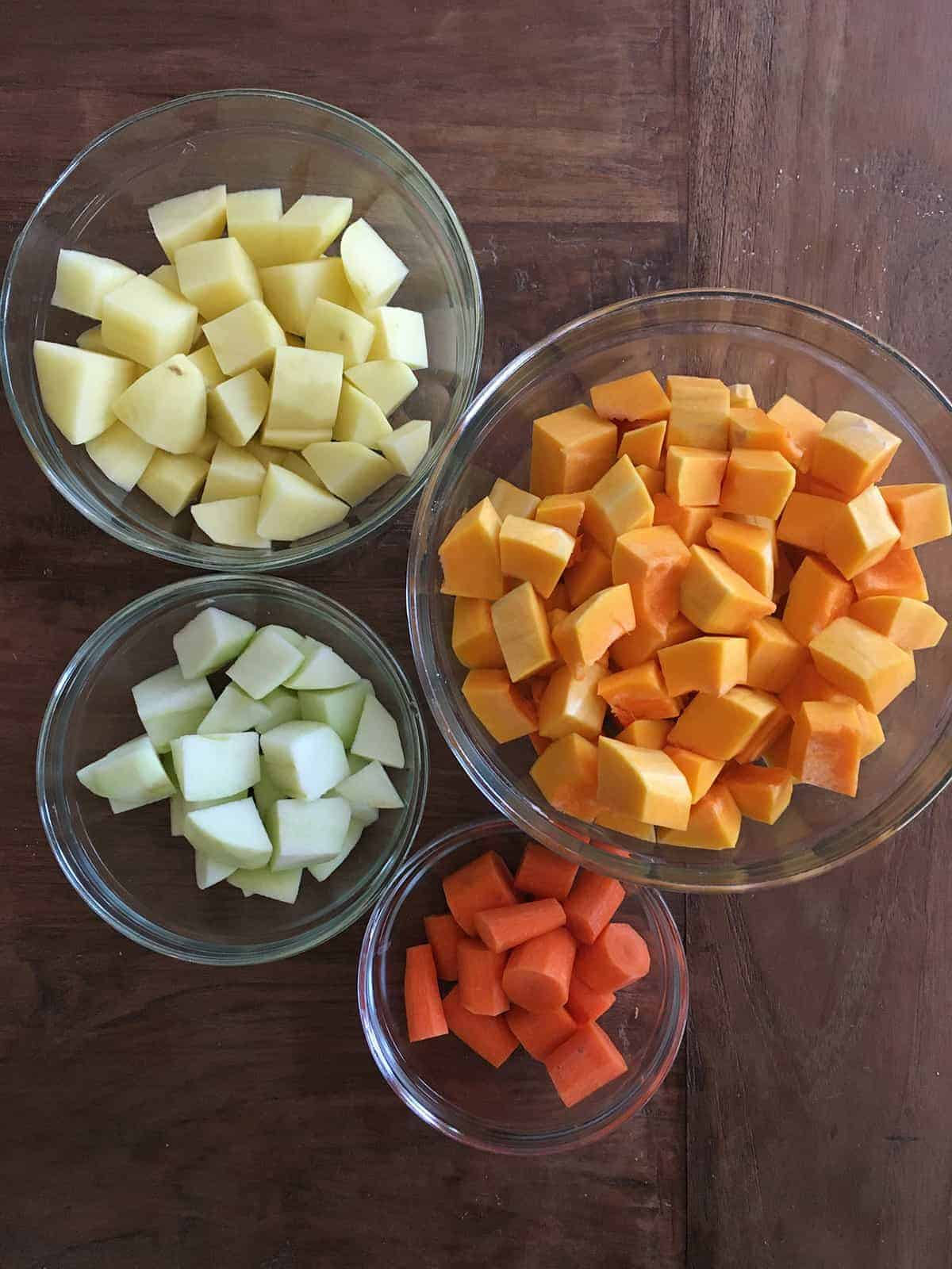 Chopped potatoes, butternut squash, apples and carrots in glass food prep bowls atop a wood table