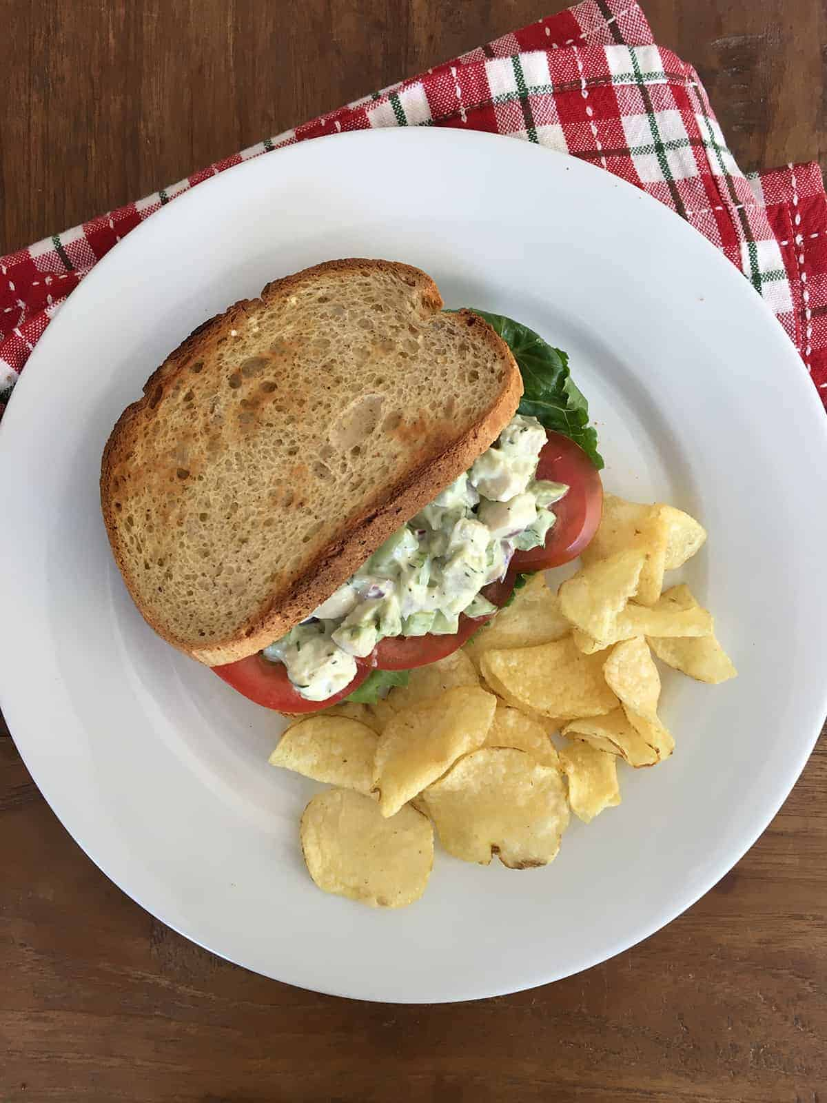 Chicken salad with avocado in a sandwich with toasted whole-grain bread, sliced tomatoes and Romaine lettuce and a side of potato chips
