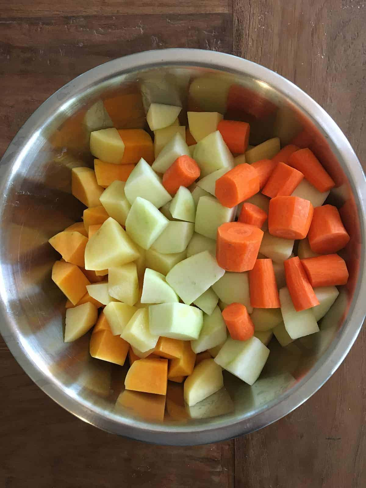 Chopped butternut squash, potatoes, apples and carrots in a stainless steel bowl