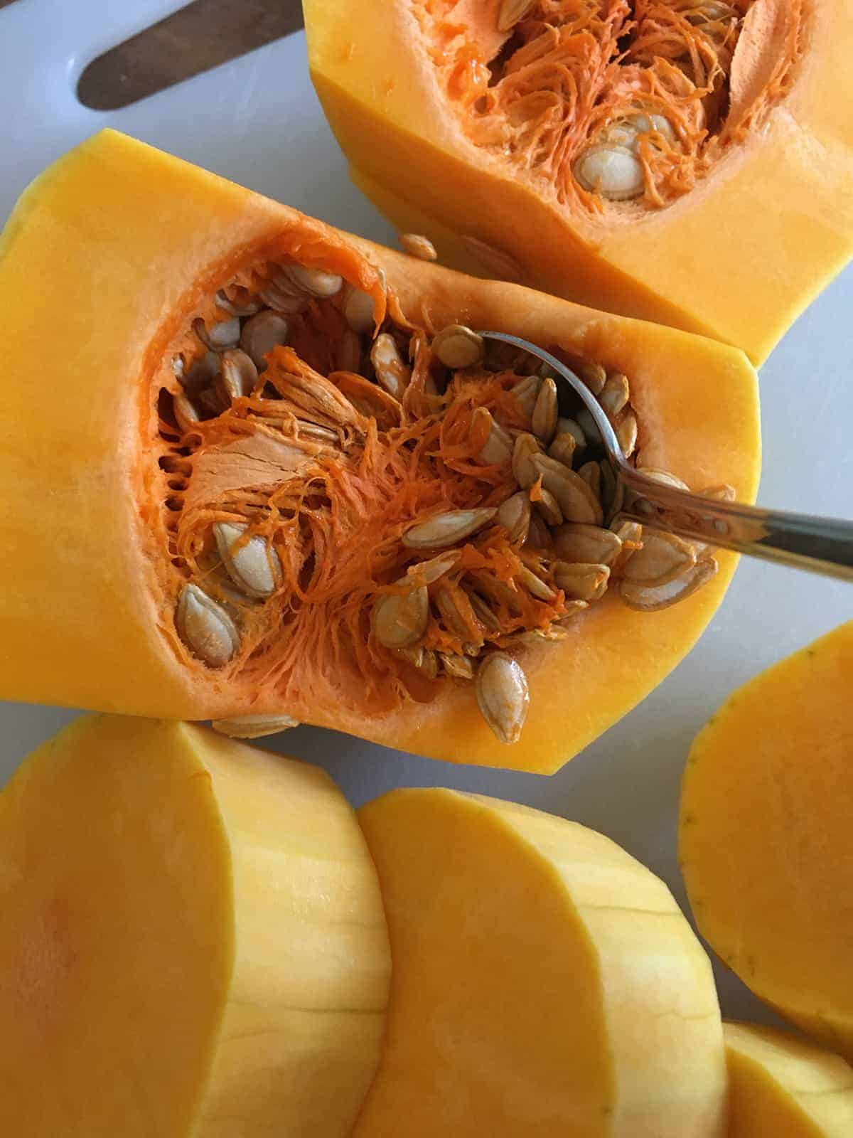 Removing the seeds from a butternut squash using a metal spoon