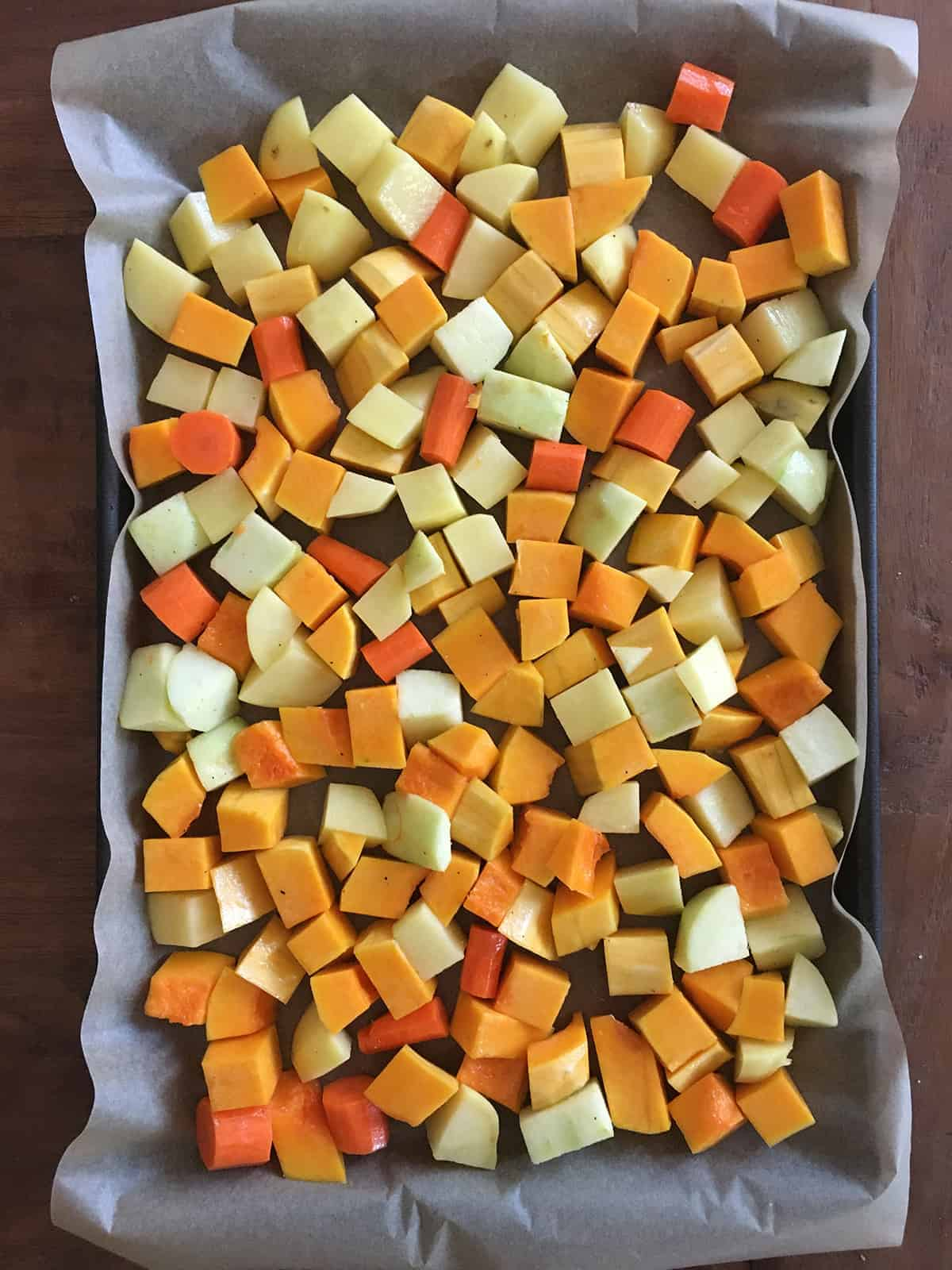 Chopped veggies and apples on a metal sheet pan lined with parchment paper