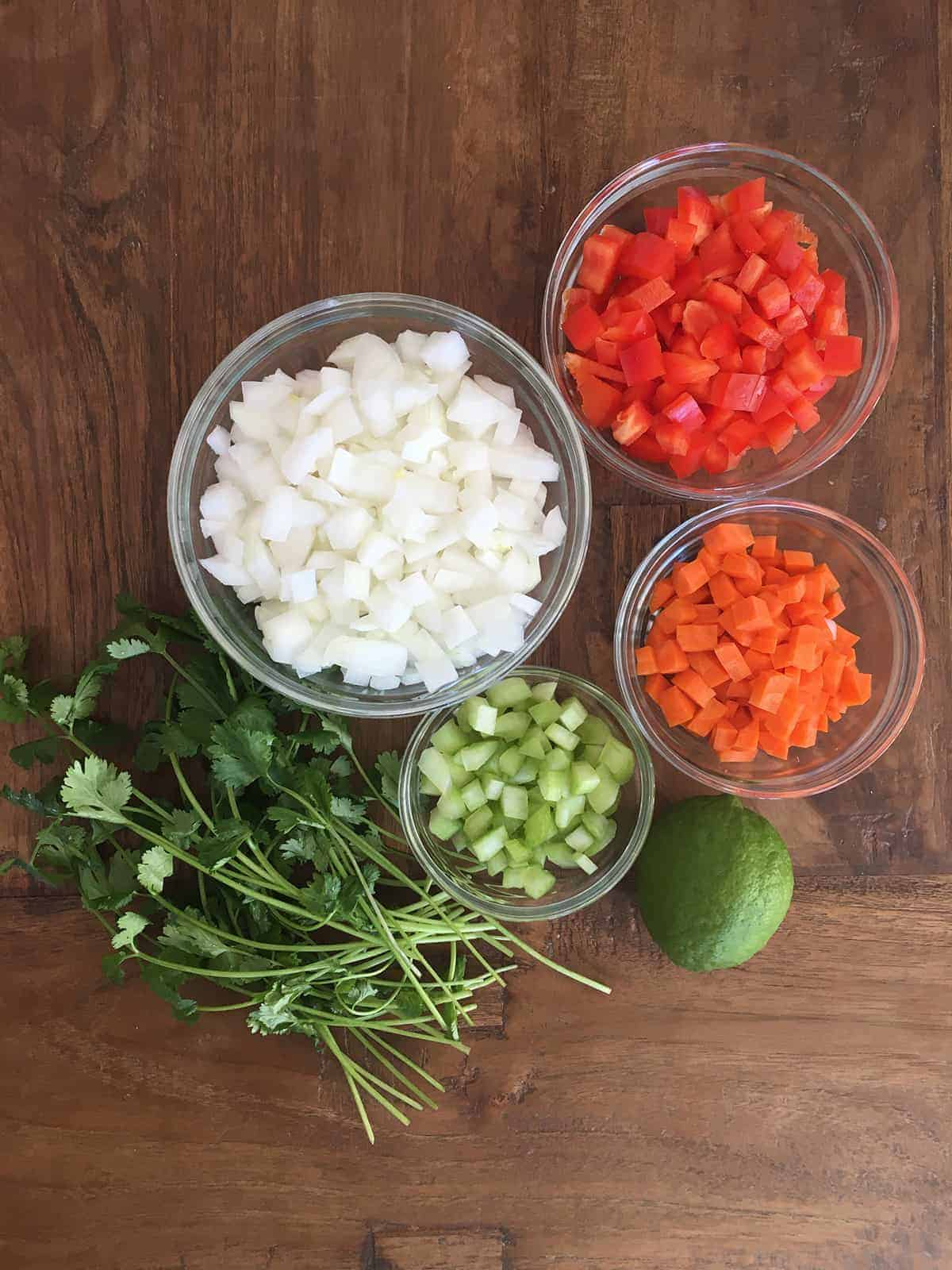 Fresh cilantro and lime alongside glass food prep bowls containing chopped onions, red pepper, carrots and celery