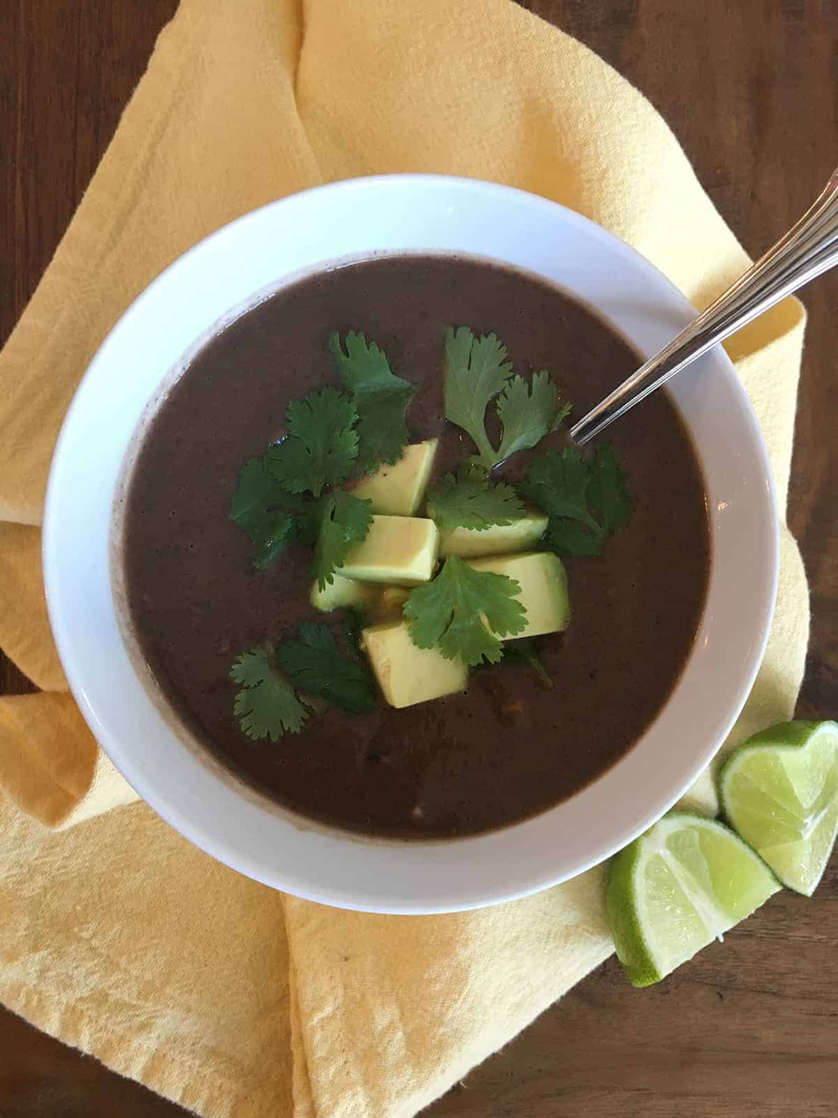 Black bean soup topped with avocado and cilantro in a white bowl with a yellow cloth napkin