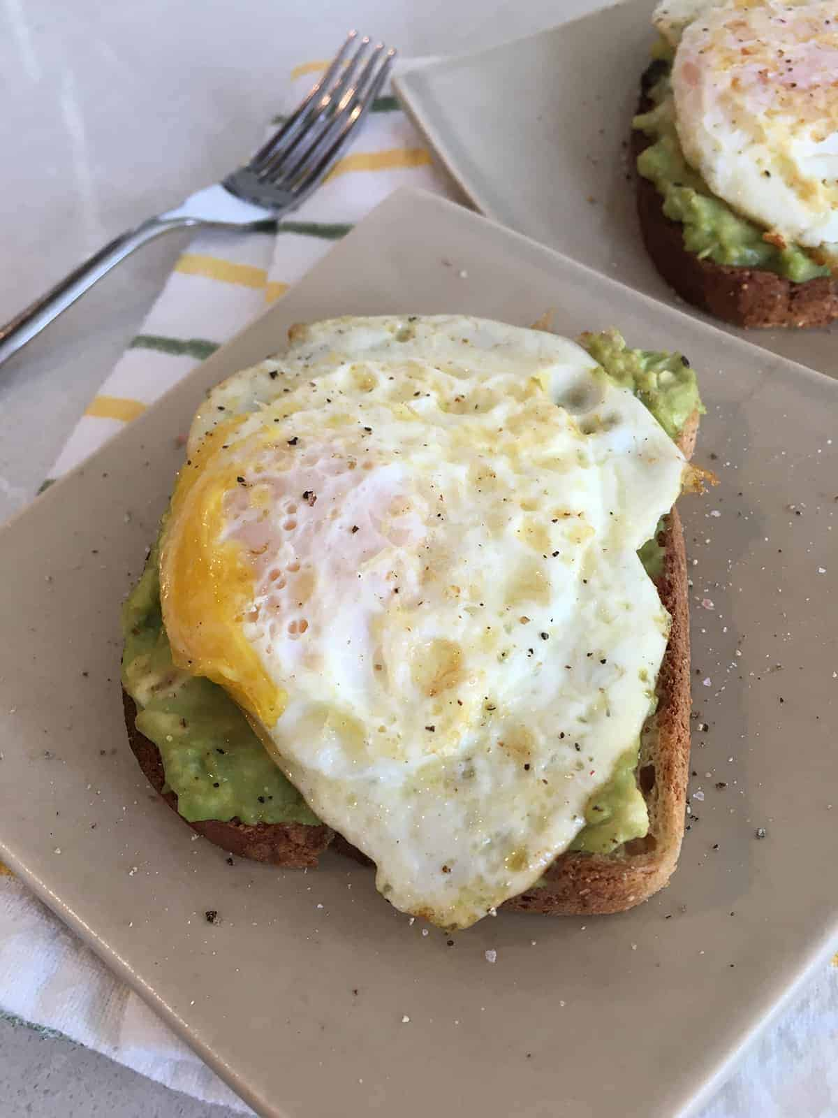 Avocado toast with egg on tan ceramic plates atop a light grey marble countertop