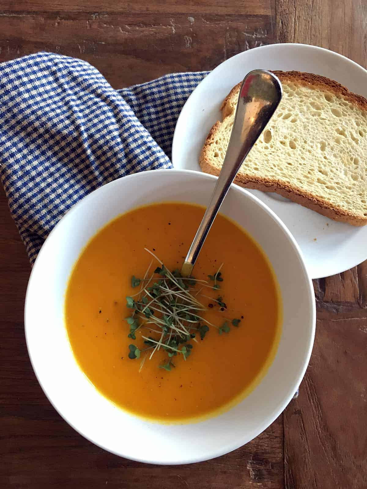 Carrot ginger soup topped with microgreens in a white bowl with a slice of bread on the side