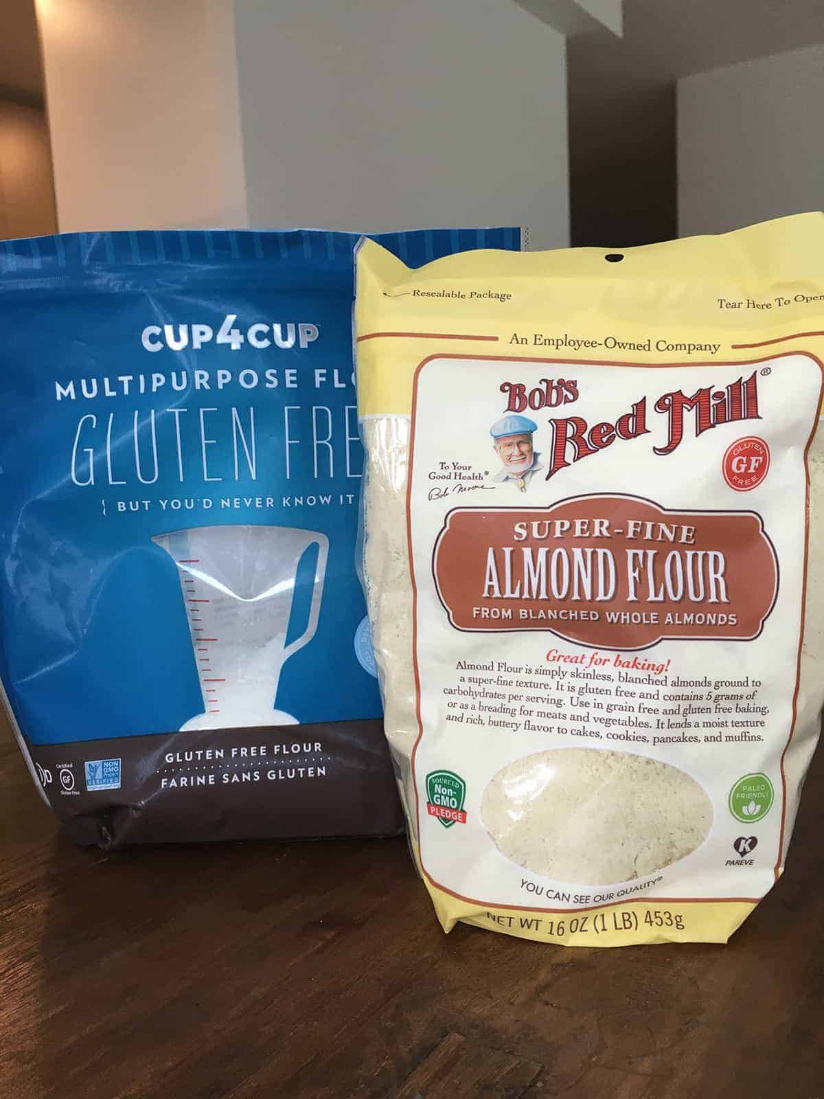 Bags of Cup4Cup Gluten Free Flour and Bob's Red Mill Super-Fine Almond Flour on a brown table