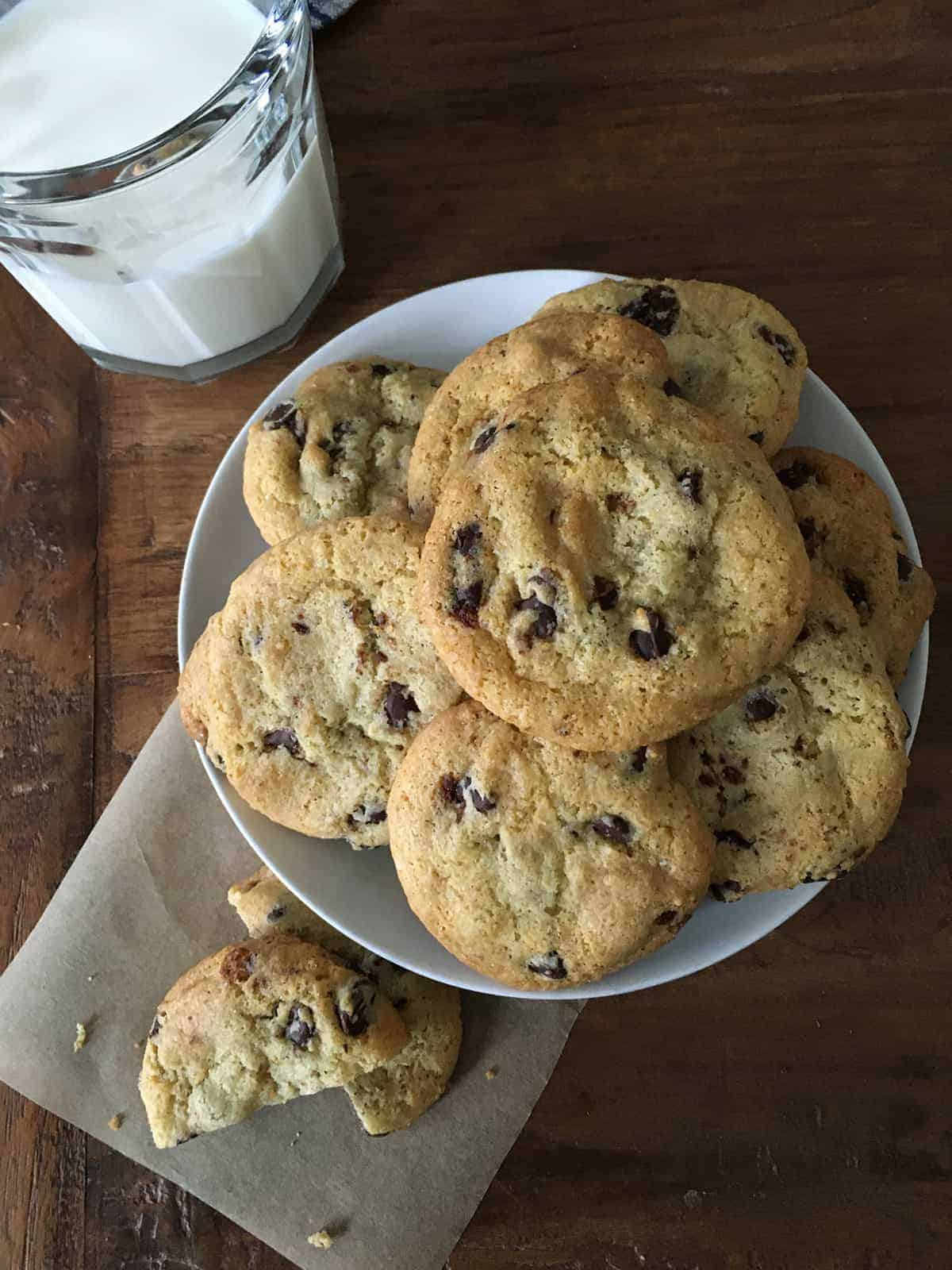 Gluten-free chocolate chip cookies with a glass of milk on a brown table