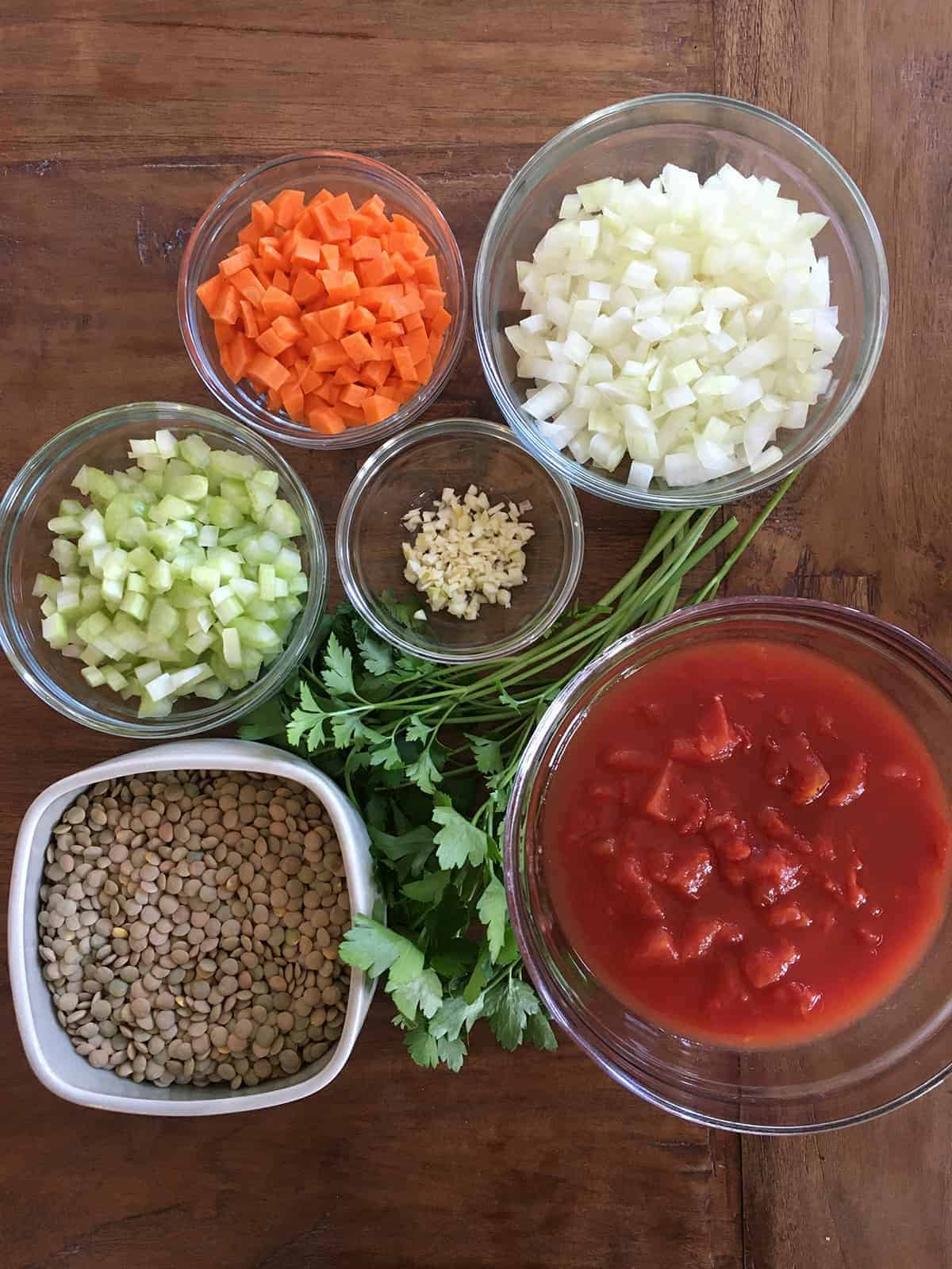 Chopped celery, carrots, onions and garlic in glass food prep bowls alongside green lentils, diced tomatoes and fresh parsley