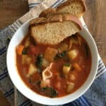 Minestrone soup and toasted bread in a white bowl