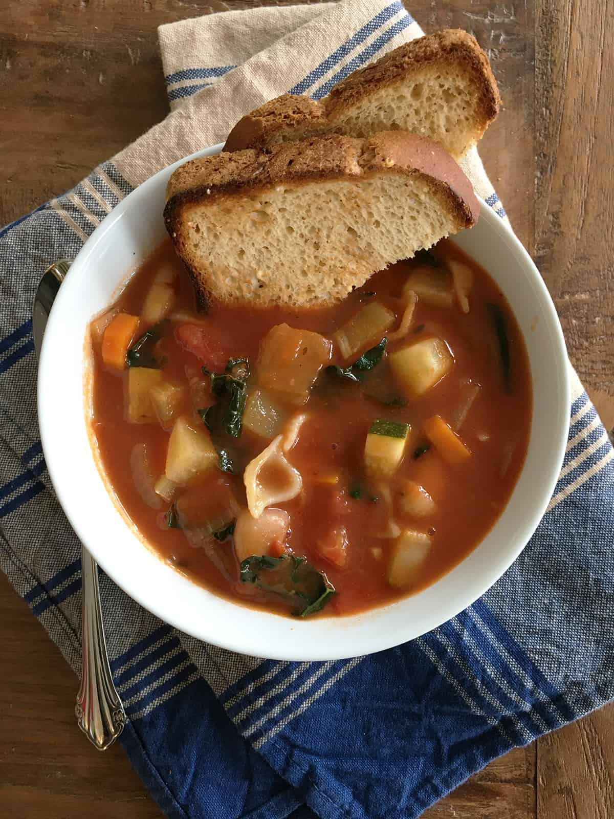 Minestrone soup and toasted bread in a white bowl atop a brown wood table
