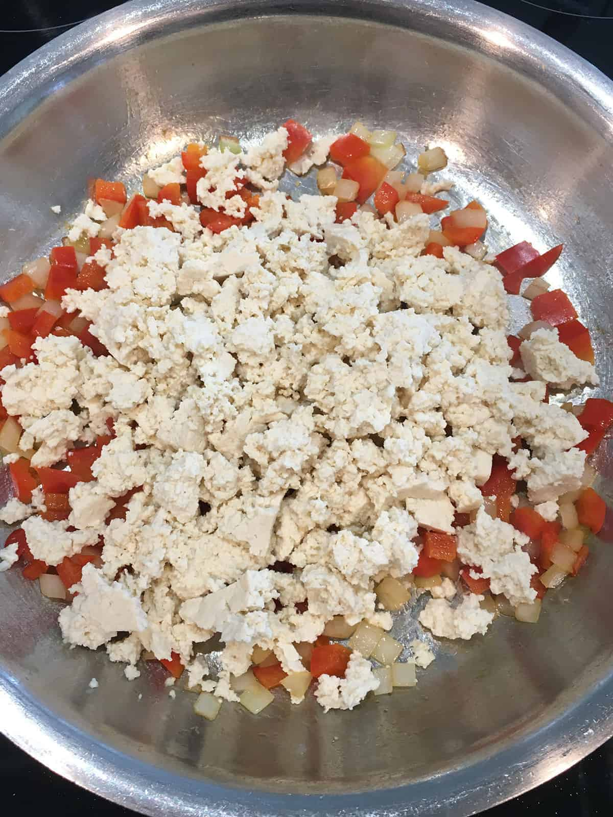 Crumbled tofu on top of cooked onion and red bell pepper in a stainless steel skillet