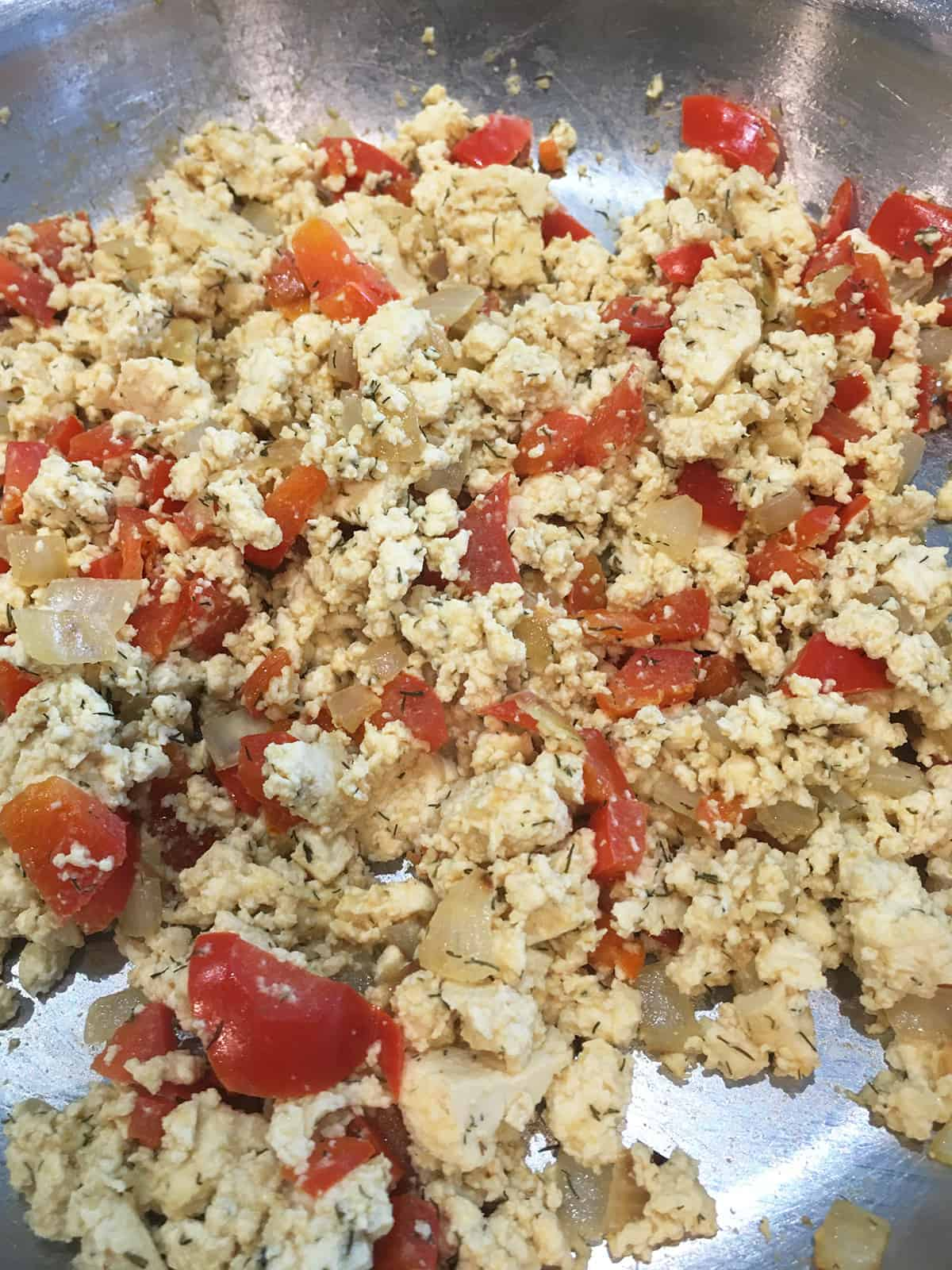Close up of cooked tofu scramble with red pepper and onions in a stainless steel pan