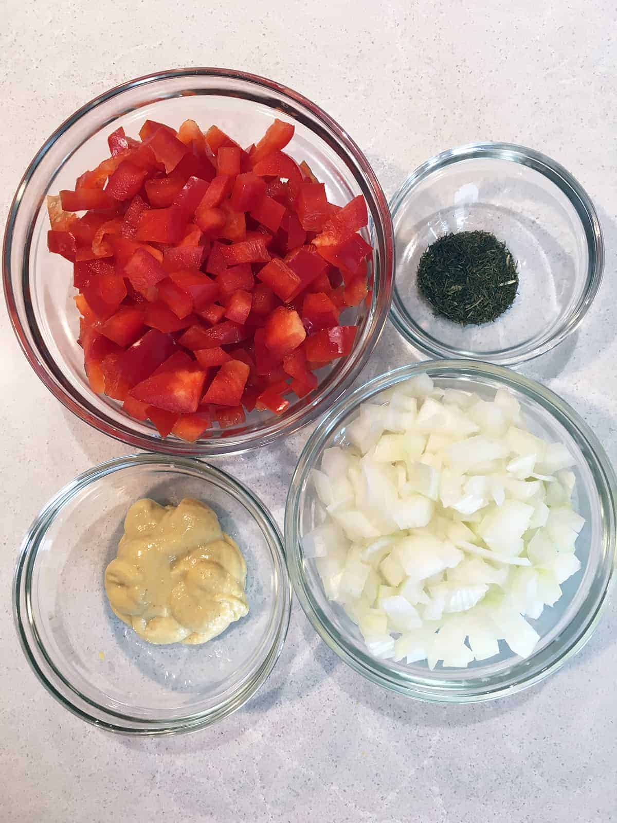 Diced red pepper and white onion alongside dried dill and Dijon mustard in glass food prep bowls