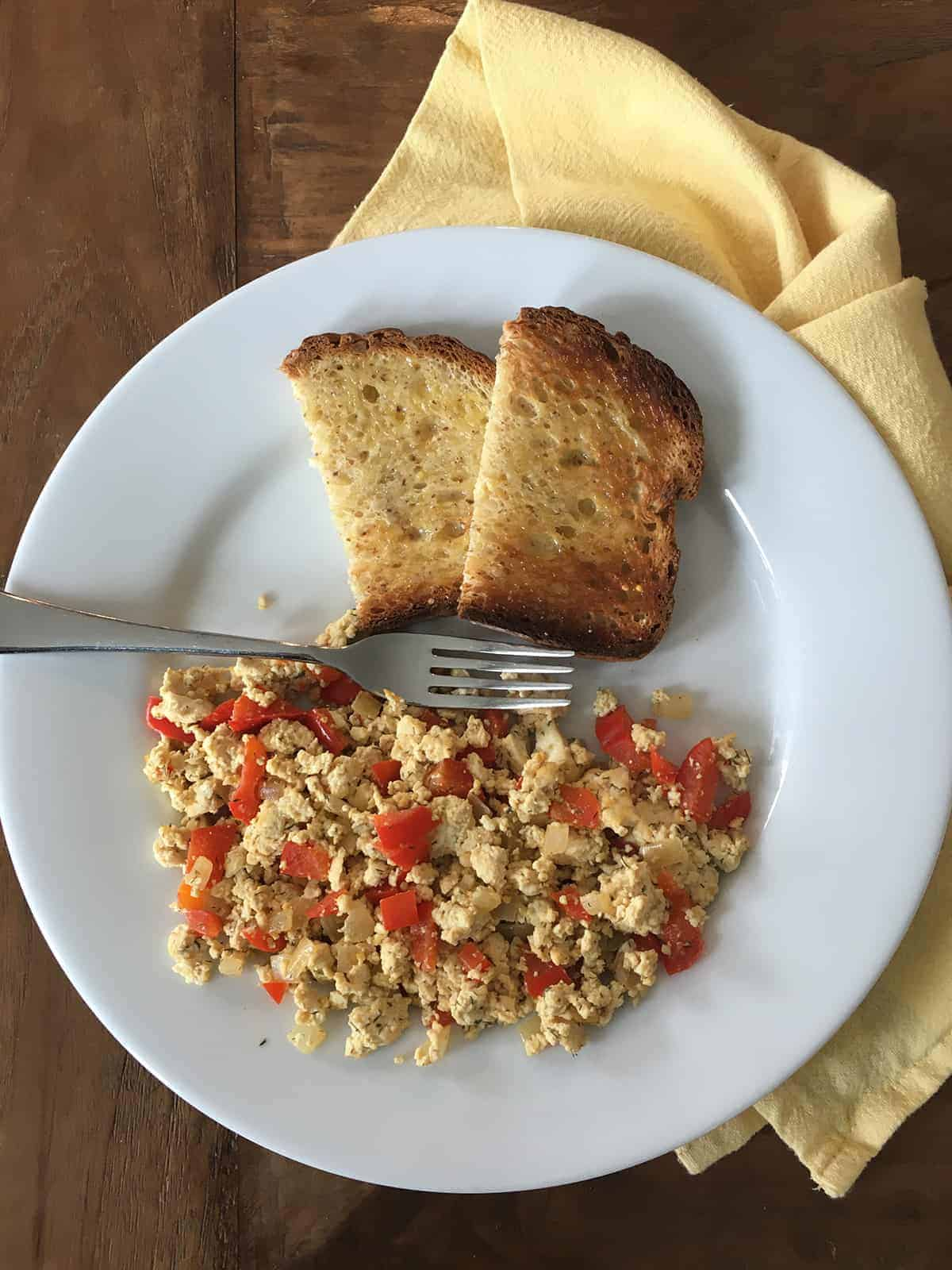Tofu scramble with toast on a white plate with a yellow napkin