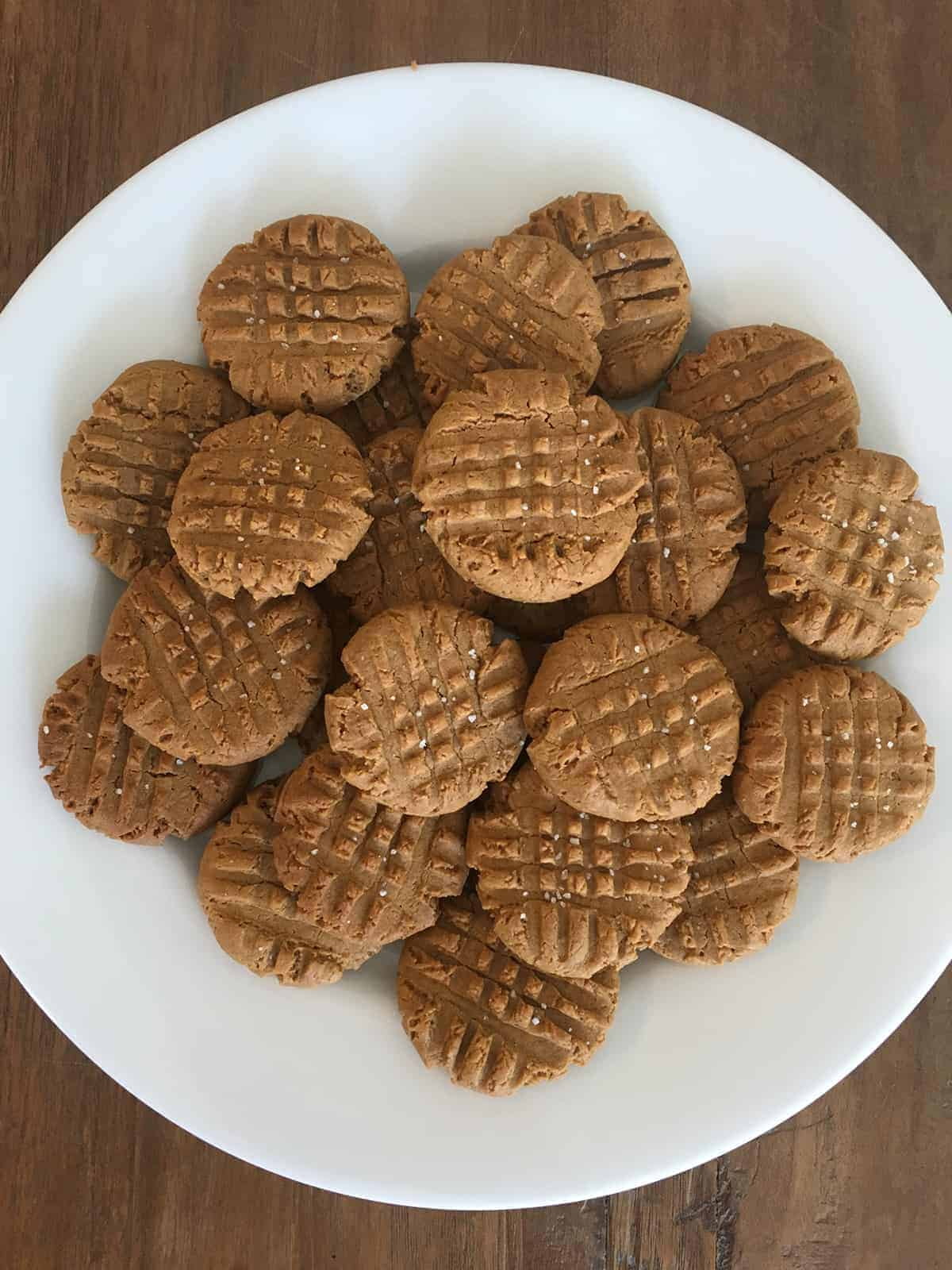 3 ingredient peanut butter cookies on white plate atop a brown table