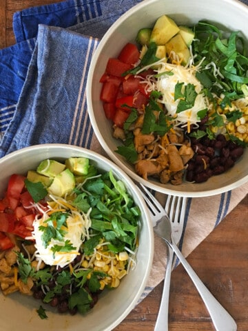 Two citrus chicken burrito bowls with a blue and tan striped napkin