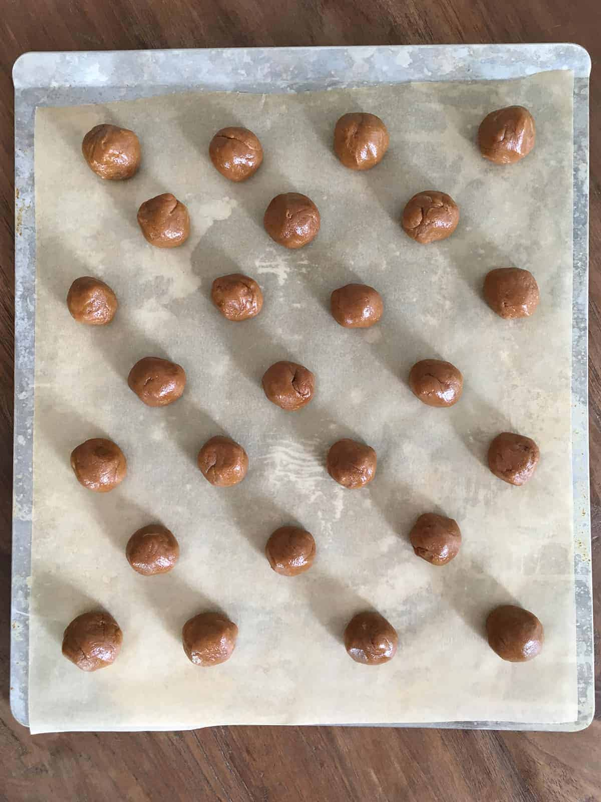 Peanut butter cookie dough balls on a stainless steel baking sheet lined with parchment paper