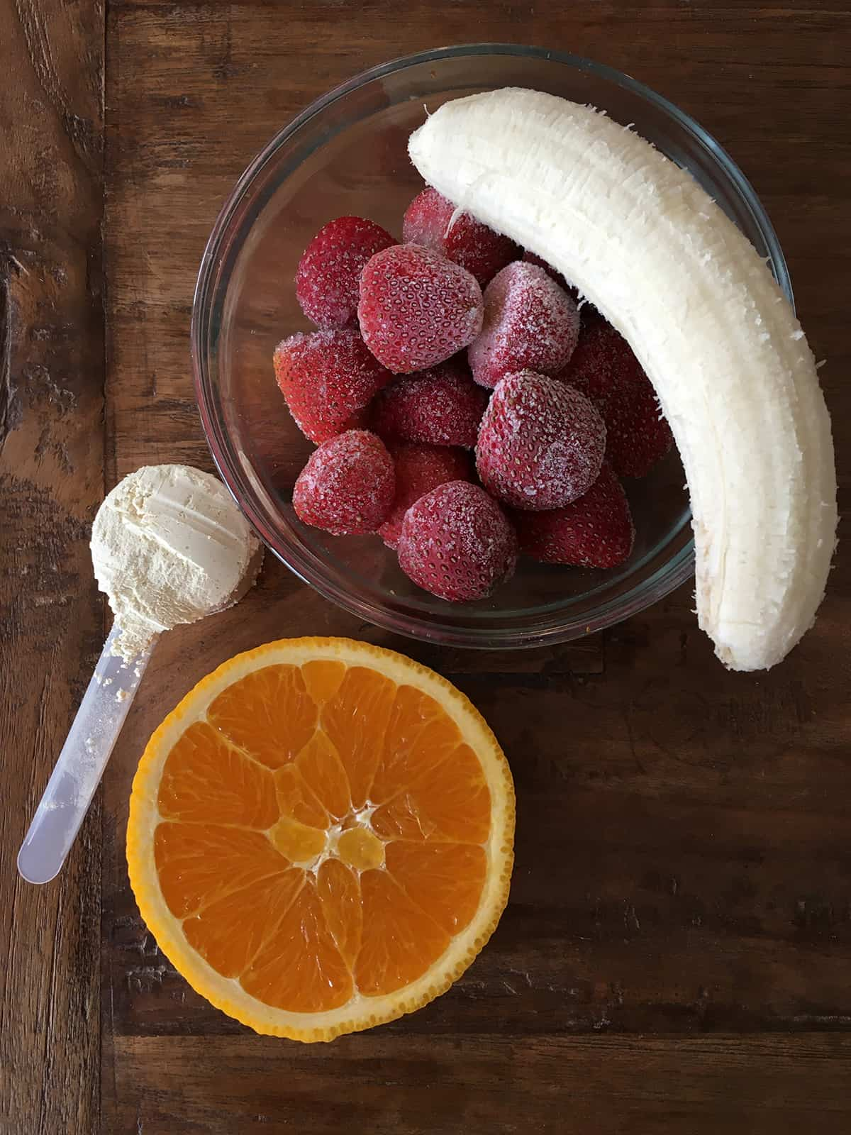 Frozen strawberries, peeled banana, half an orange and a scoop of protein powder on a brown wood table