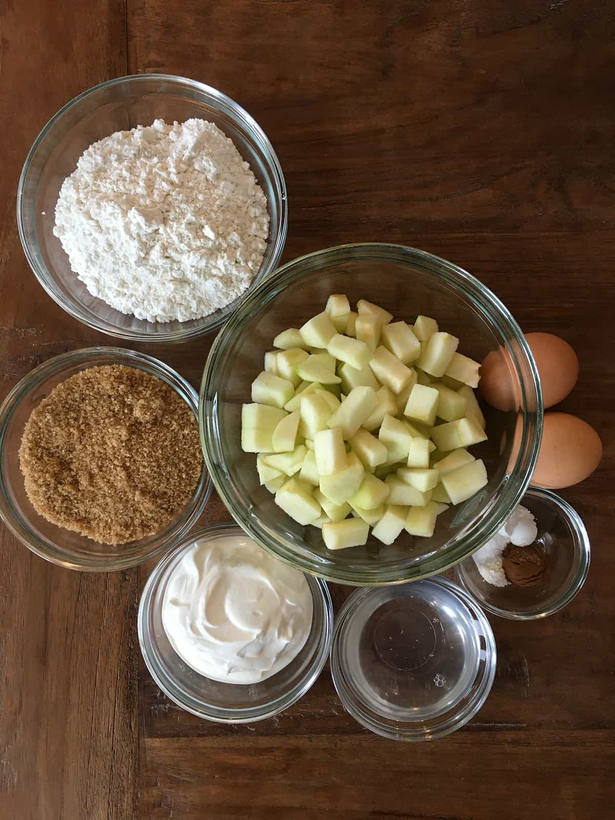 Flour, brown sugar, sour cream, coconut oil, spices and chopped apples in glass bowls alongside two brown eggs