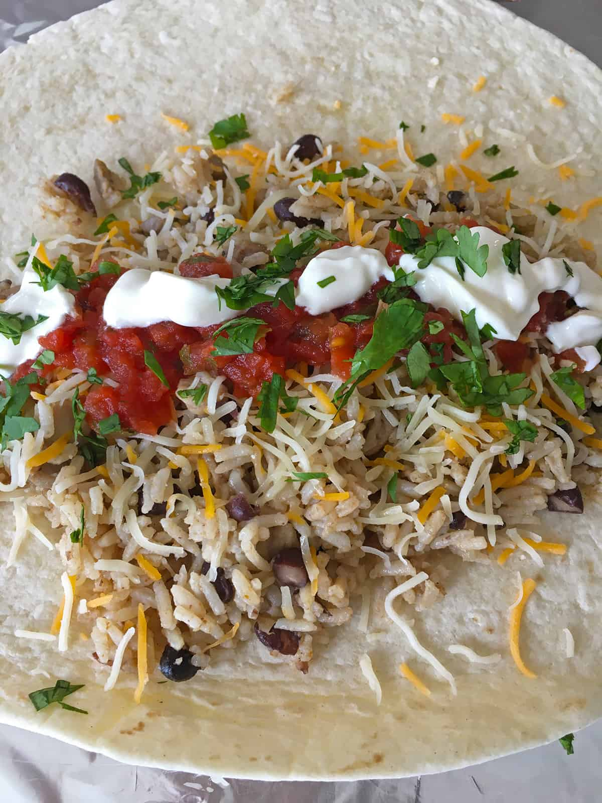 Topping chicken burritos with shredded cheese, salsa and sour cream just before rolling up