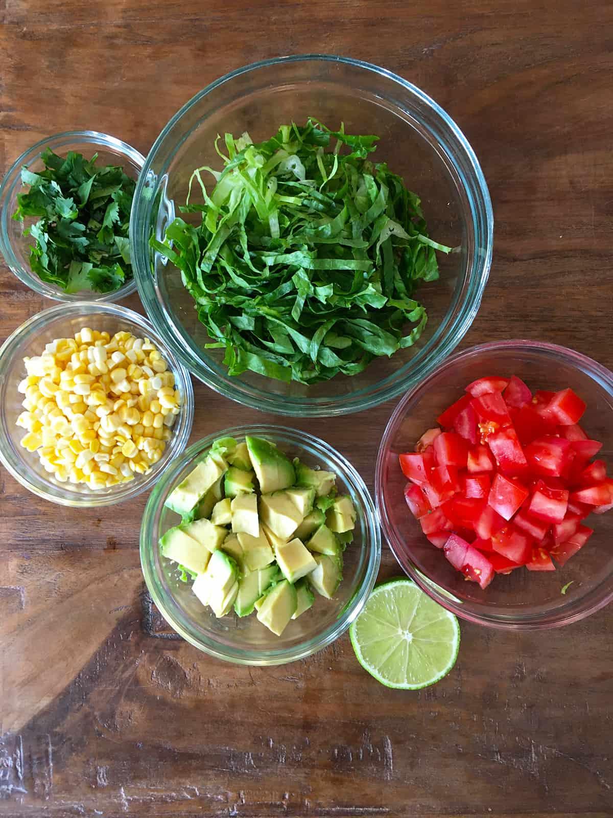 Chopped romaine lettuce, cilantro, corn, avocado and tomato in glass food prep bowls alongside half a lime
