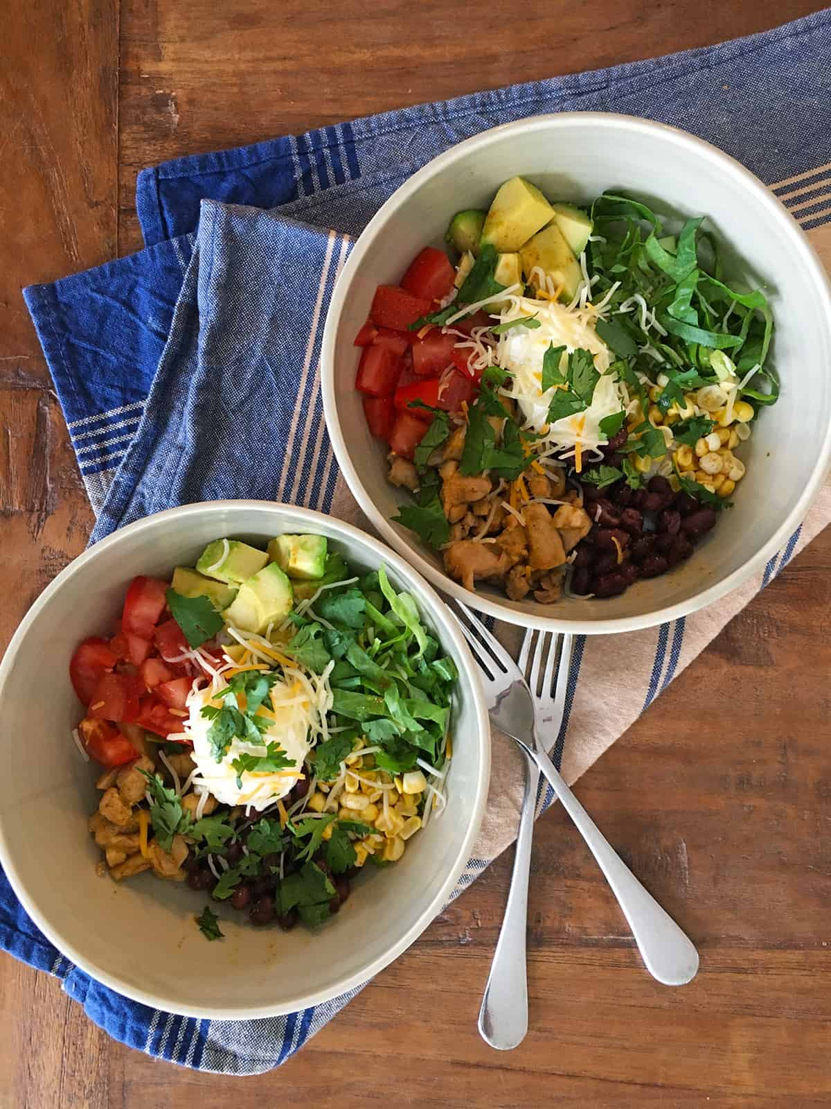 Two citrus chicken burrito bowls with a blue and tan striped napkin on a brown wood table