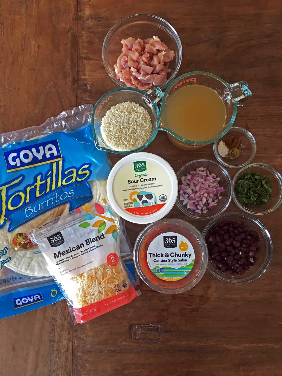 Chicken burrito ingredients on a wood table including rice, black beans, sour cream, salsa and shredded cheese