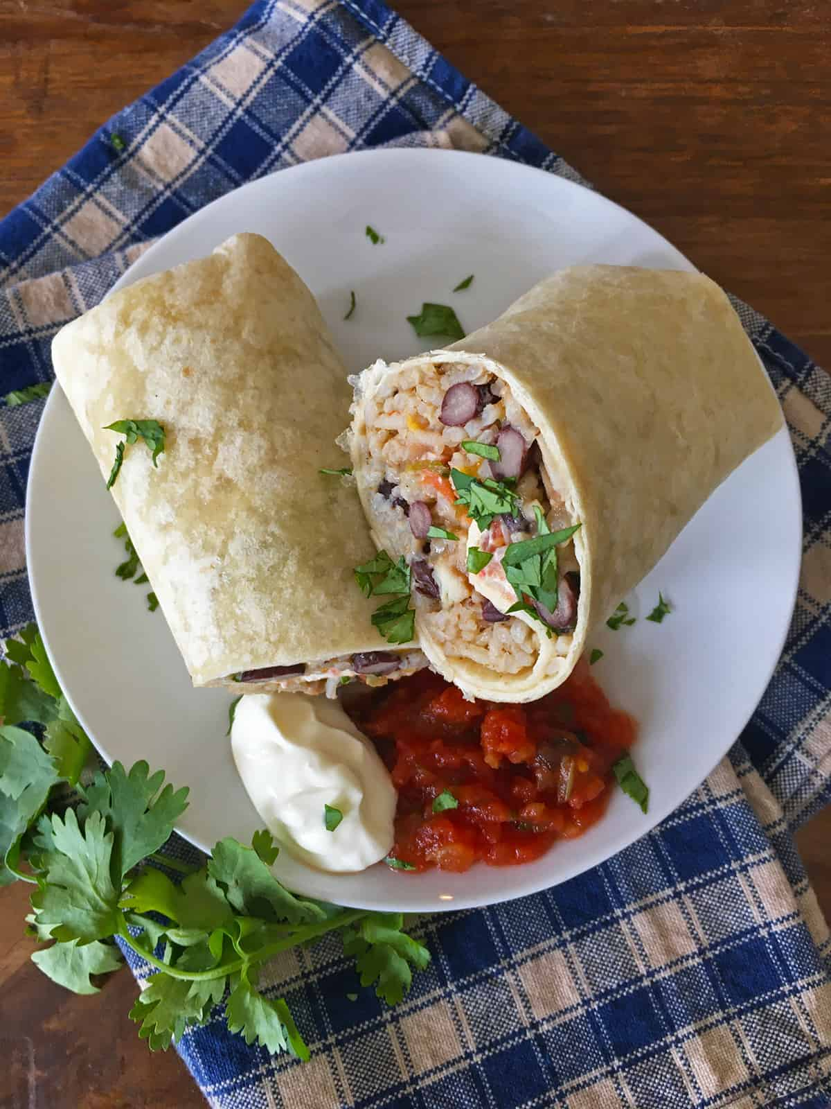 Chicken burrito with salsa and sour cream on a white plate with a blue and tan checkered napkin