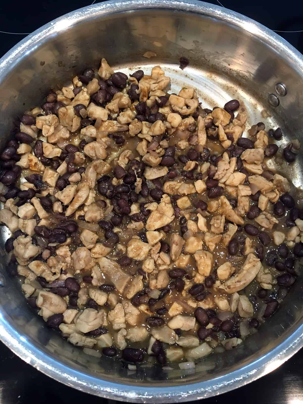 Cooking chicken, black beans, onions, chicken broth and spices in a stainless steel pan