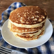 Stack of gluten free pancakes on a white plate